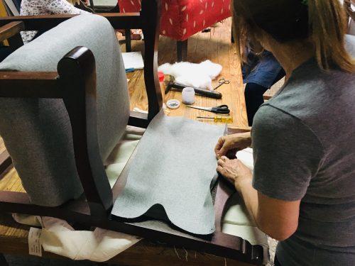 mujer tapiza respaldo de un sillon